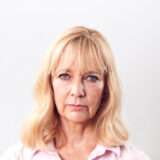 Studio Shot Of Unhappy And Frustrated Mature Woman Against White Background At Camera