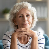 Head shot portrait attractive mature 60s woman put chin on hands posing looking at camera seated on couch in light living room at home, concept of care beauty treatment for seniors women, retired life